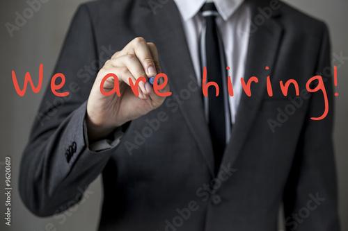 Fotografía  Businessman writing 'We're hiring' tab on virtual screen