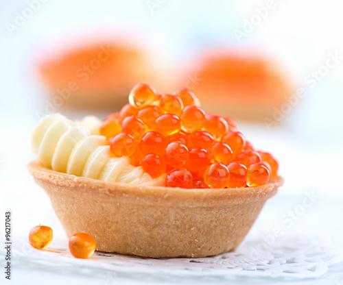 Tartlet with red caviar closeup. Gourmet food