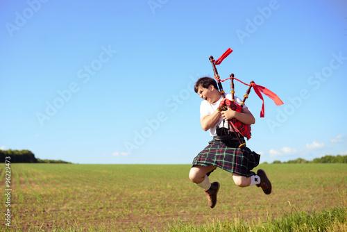 Photo de sauter haut mâle avec des tuyaux en kilt traditionnel écossais sur vert Poster Mural XXL