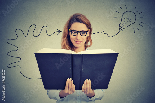 Fotografía  Woman in glasses reading big book comes up with an idea