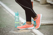 Urban fitness lifestyle and sportswear concept. Sport running shoes and bottle of water close up.