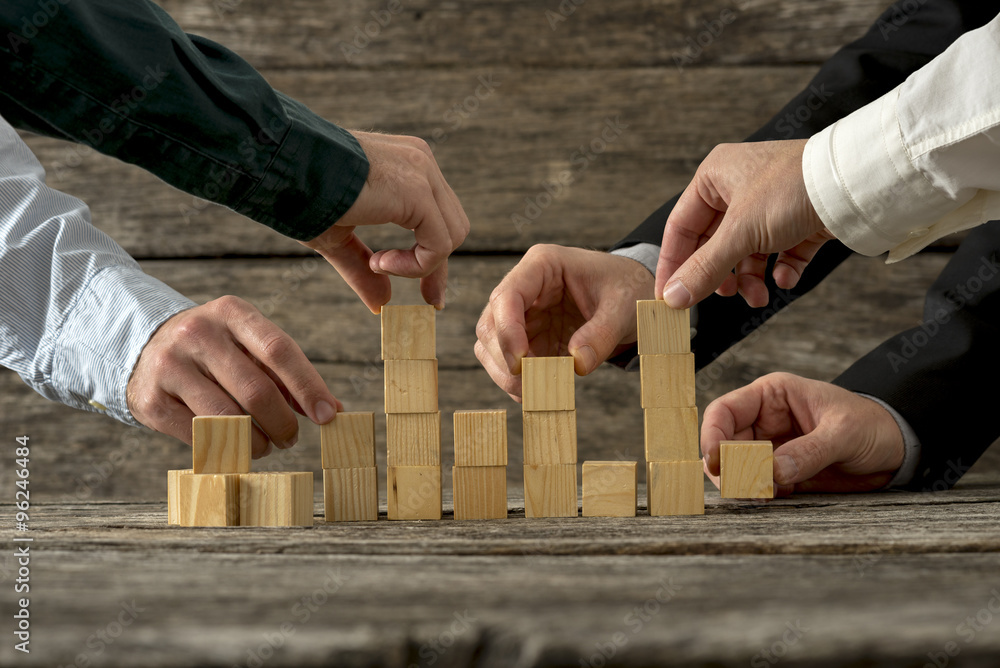 Fototapeta Hands of five businessman holding wooden blocks placing them int