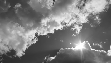 Fototapeta in the sky the sun breaks through the clouds. Black and white photo