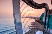 Close Up Of The Hands Of Woman Playing Harp By The Sea At Sunset