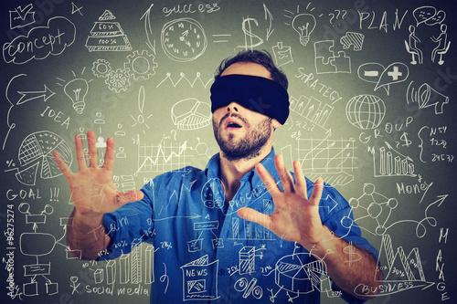 Leinwand Poster  Junger Geschäftsmann mit verbundenen Augen, der das Gehen durch Finanzdatenplan
