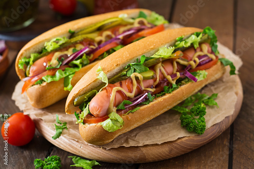 Carta da parati Hot dog with pickles, tomato and lettuce on wooden background