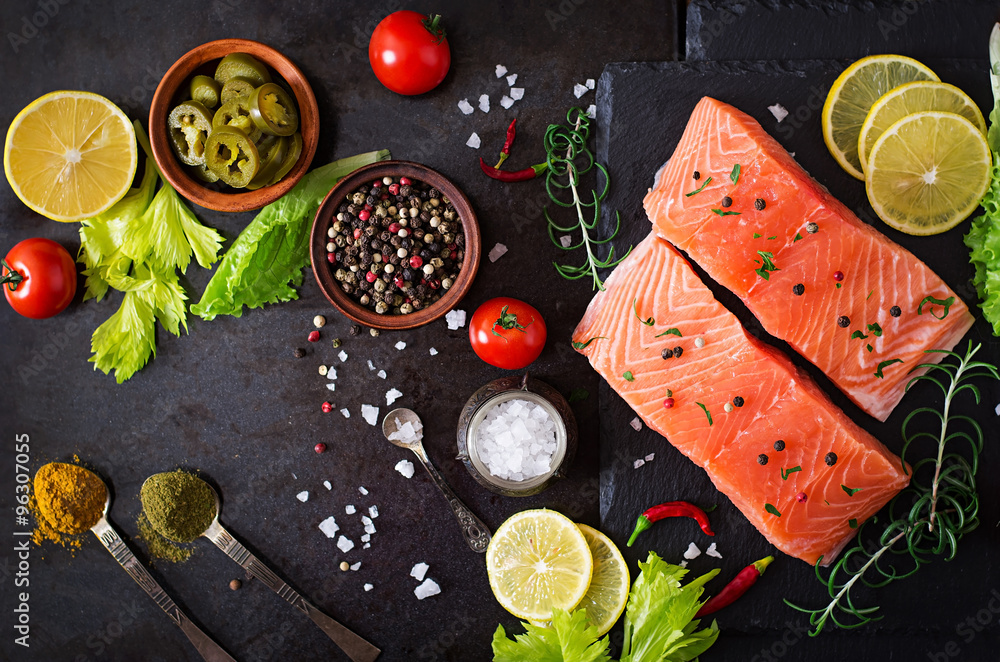 Fototapeta Raw salmon fillet and ingredients for cooking on a dark background in a rustic style. Top view