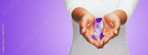 close up of hands holding purple awareness ribbon Fototapeta