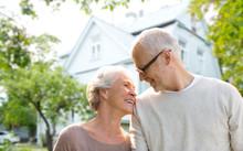 Senior Couple Hugging Over Living House Background