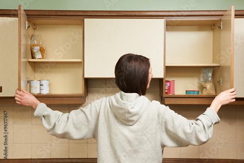Woman Looking In Empty Food Cupboards Canvas Print