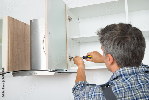 Photo  Serviceman Fixing Cabinet With Screwdriver In Kitchen
