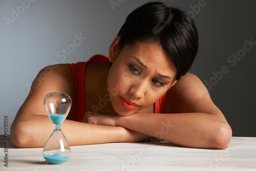 Fotografiet  Sad Young Woman Looking At Hourglass