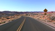 Driving USA: Car driving POV along an empty desert road through the Valley of Fire, Nevada. Beautiful desert landscape and views to distant sandstone mountains