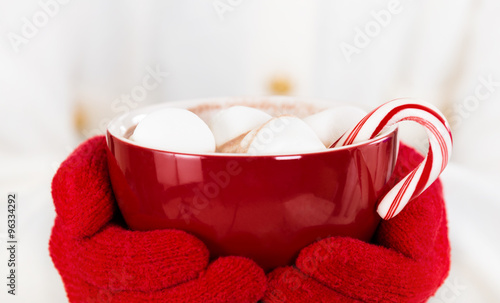 Red gloved hands holding a red cup of hot chocolate with marshmallows and a candy cane