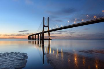 Obraz na Szkle Ponte Vasco da Gama ao anoitecer com iluminação.