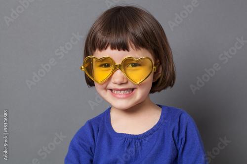 17c6a16cd7d1 fun kid glasses concept - ecstatic preschool child wearing yellow  heart-shape glasses for comic