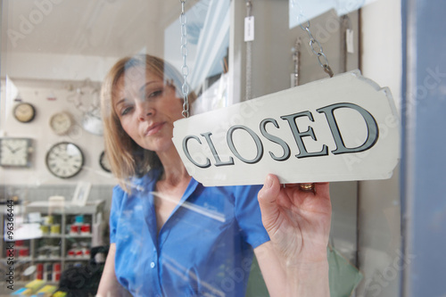 Fotografering  Store Owner Turning Closed Sign In Shop Doorway