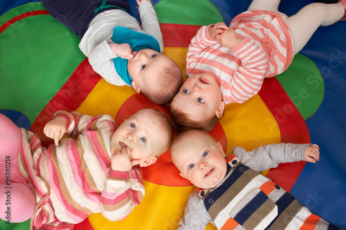obraz lub plakat Overhead View Of Babies Lying On Mat At Playgroup