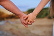 Young people are a pair of lovers in the sand and hold hands