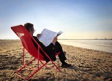 Businessman Reading The Newspaper At The Seaside