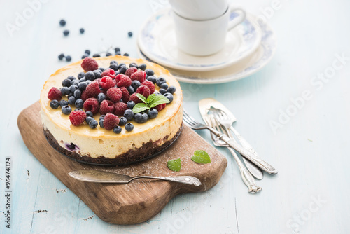 Valokuva  Cheesecake with fresh raspberries and blueberries on a wooden serving board, pla