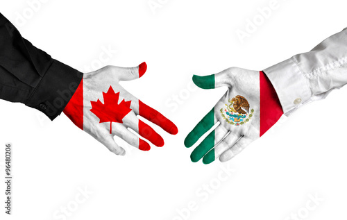 Fotomural  Canada and Mexico leaders shaking hands on a deal agreement