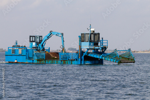 Fotografia, Obraz  Close up of a blue dredger working on italian Po river lagoon
