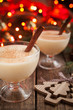 Eggnog traditional homemade christmass celebration egg, milk, rum, vanilla liqueur alcohol drink with cinnamon stick in two glass cups on vintage wooden table. Red bokeh and shallow depth of field