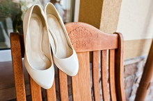 Cream Wedding Shoes Of Bride On Wooden Chair