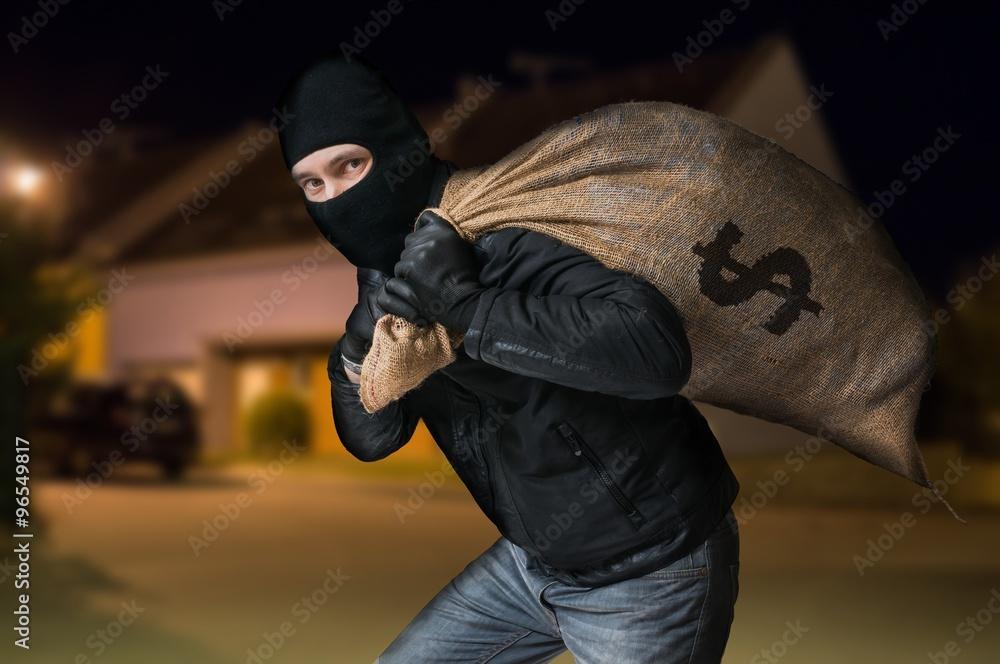 Fototapeta Robber is running away and carying full bag of money at night.