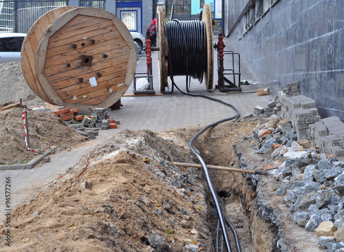 Fotografía  Wooden coil of electric cable and optical fibres in the digging on the street co