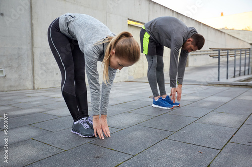 Fotografia couple stretching and bending forward on street