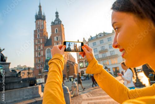 Fototapeta Female traveler photographing with mobile phone in Krakow obraz