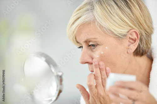 Fotografía  Senior woman in bathroom applying anti-aging lotion
