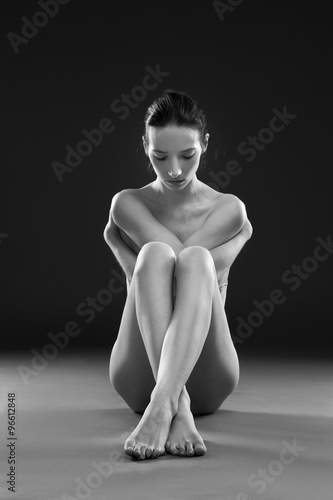 Fotografering  Naked yoga. Beautiful sexy body of young woman on gray background