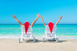 Couple in Santa hats relaxing at beach on sun beds