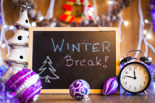 Fotografie, Obraz  Winter Break written on the black chalkboard with Christmas decorations and ligh
