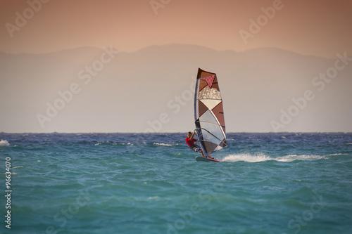 obraz PCV Windsurfen in Rhodos Griechenland. Mann surft im blauen Meer vor rötlichem Himmel, Insel im Hintergrund.
