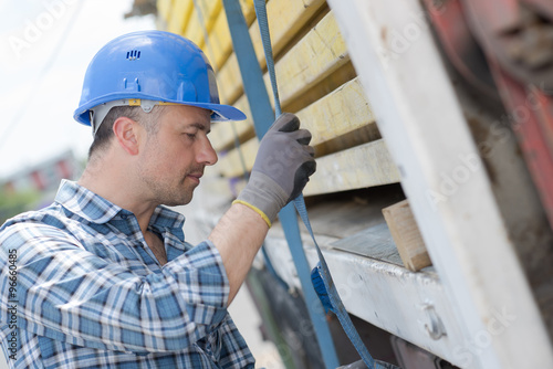 Fotografía  Man securing straps to side of lorry