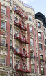 Red fire escapes on old building in the city of New York.