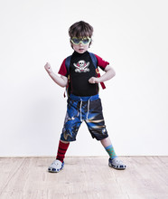 A Boy Standing With His Legs Apart Posing In Fancy Dress, Wearing A Pirate Tee-shirt, Eye Goggles And Long Shorts.