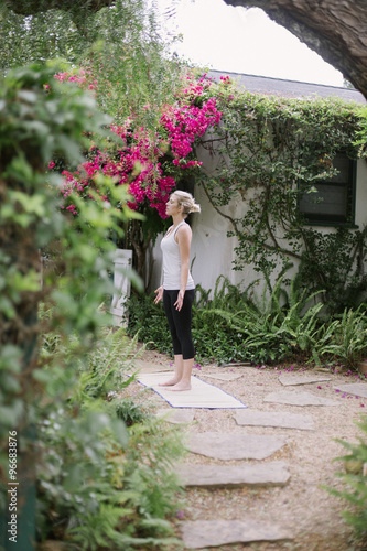 Papiers peints Jardin Blond woman doing yoga in a garden.