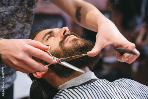 Hairdresser doing haircut of beard to young attractive man Poster