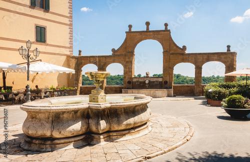 Fotomural Ancient Fountain and arches in Repubblica square, in Pitigliano,