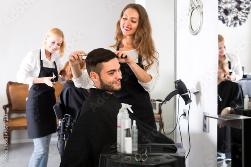 Young hairdresser cutting hair in salon