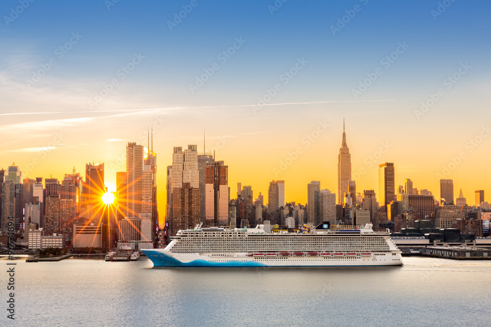 Fototapety, obrazy: New York City skyline at sunrise, as viewed from Weehawken, along the 42nd street canyon. A large cruise ship sails Hudson river, while sun beams burst between the skyscrapers.