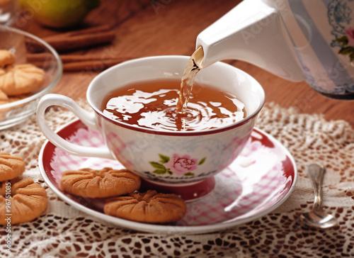fototapeta na lodówkę versare il tè caldo nella tazza di porcellana