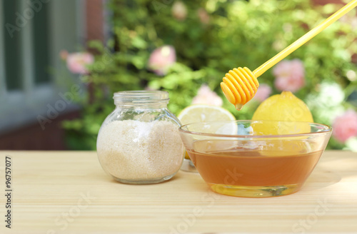 Photo  Bowl of honey and sugar and lemons on wooden table