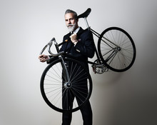 Portrait Of A Handsome Middle Aged Man Wearing Suit And Holding His Classic Bicycle On The Shoulder