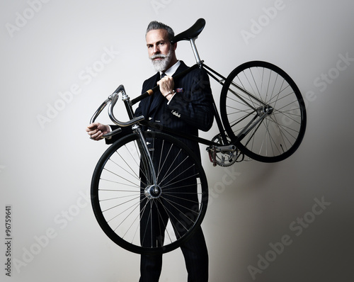 Fotografie, Obraz  Portrait of a handsome middle aged man wearing suit and holding his classic bicy